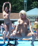 Multiple naked strippers on stage at an ourdoor public nudity party